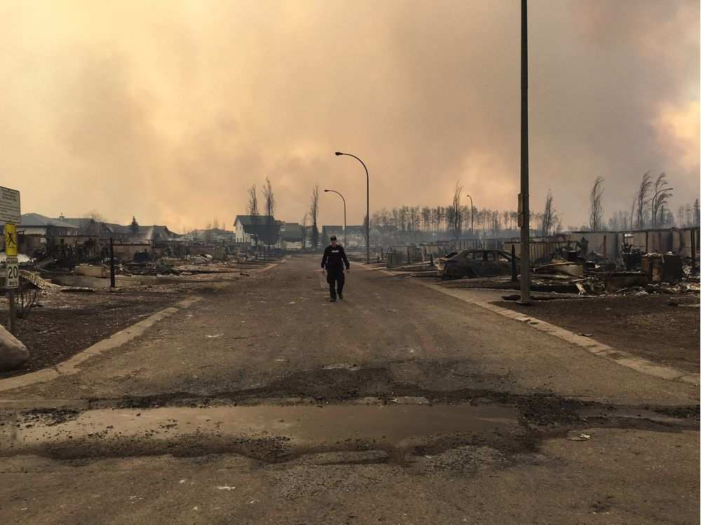a-mountie-surveys-the-damage-on-a-street-in-fort-mcmurray-m